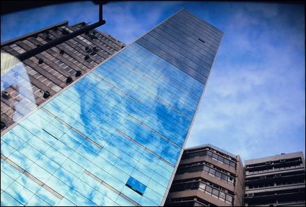 השתקפות של בניין על אוטובוס בהונג קונג