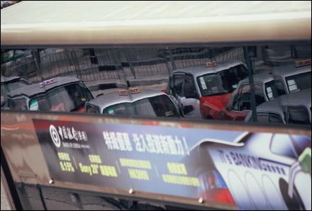 מוניות משתקפות על פני אוטובוס קומותיים בהונג קונג